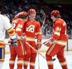 Hockey Photos - Atlanta Flames - Tom Lysiak (l.) celebrates with Dave Shand and Harold Phillipoff after a goal against the Colorado Rockies in 1978