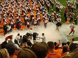 "College Football Photos - Syracuse Orange - Former football head coach Greg Robinson ""chases"" the last of his players onto the field before the kickoff of his inaugural 2005 season. It was also the first game played on the Carrier Dome's new FieldTurf."