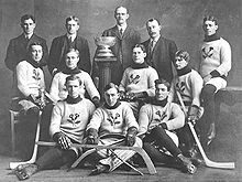 Hockey Photos - Art Ross - The Kenora Thistles posing for a photo with the Stanley Cup in 1907. Ross is in the front row
