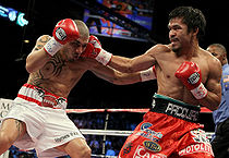 Boxing Photos - Manny Pacquiao - Pacquiao throws a right hook at Cotto.