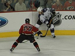 Hockey Photos - Nhl - Los Angeles Kings' Mike Weaver battling for the puck against Calgary Flames' Daymond Langkow