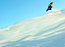 Sports Photos - Extreme Sports - Snowboarder drops off a cornice.