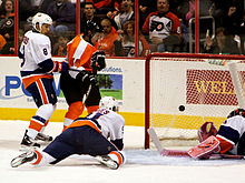 Hockey Photos - Daniel Briere - Daniel Brière (centre) watches a goal go in against the New York Islanders.