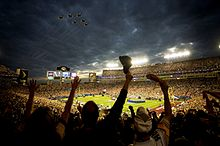 Football Photos - 2009 SUPER BOWL XLIII - Fans wave as the U.S. Air Force Thunderbirds fly over the stadium during the pregame ceremony.