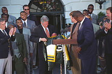 Football Photos - 1997 SUPER BOWL XXXI - Brett Favre and Reggie White (front) present a Packers jacket to President Bill Clinton in May 1997.