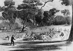 Sports Photos - Australian Rules Football - A game at the Richmond Paddock in the 1860s. A pavilion at the MCG is on the left in the background. (A wood engraving made by Robert Bruce on 27 July 1866.)