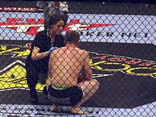 Sports Photos - Mixed Martial Arts - A ring-side doctor attends to a fighter following a loss.