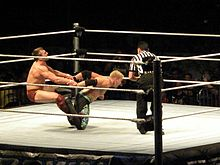 Sports Photos - Daniel Bryan - Danielson performing a surfboard on Christian.