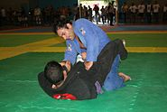 Sports Photos - Brazilian Jiu-Jitsu - The Jiu Jitsu practitioner in black is demonstrating a type of closed guard
