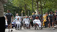 Olympics Photos - 2012 Summer Paralympics - A group of wheelchair-bound torchbearers bringing the Paralympic flame through Canary Wharf.