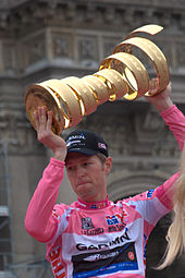 Sports Photos - Giro D'Italia - Ryder Hesjedal, the winner of the 2012 Giro d'Italia, wearing the maglia rosa and holding the winner's trophy in Milan.