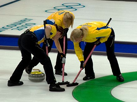 Olympics Photos - Curling - The skip of Team Sweden joins the front end in sweeping a stone into the house at the 2010 Winter Olympic Games in Vancouver