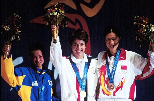 Olympics Photos - 2000 Summer Olympics - Gold medallist Nancy Johnson (centre) of the U.S., raises her hands with silver medallist Cho-Hyun Kang (left), of South Korea, and bronze winner Jing Gao (right), of China, during the first medal ceremony of the 2000 Olympic Games.