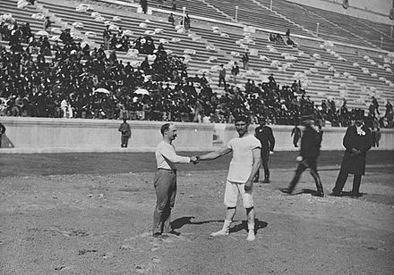 Olympics Photos - 1896 Summer Olympics - Carl Schuhmann (left) and Georgios Tsitas shake hands before the final match of the wrestling competition.