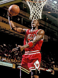 Basketball Photos - Michael Jordan - Jordan going in for a slam dunk with his signature exposed tongue.